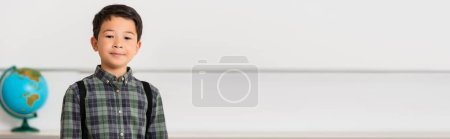 Photo for Panoramic shot of asian schoolboy looking at camera in classroom - Royalty Free Image