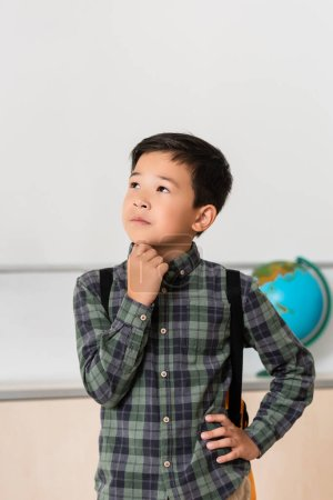 Photo for Thoughtful asian schoolboy with hand on hip in classroom - Royalty Free Image