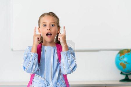 Excited schoolgirl having idea in classroom of stem school