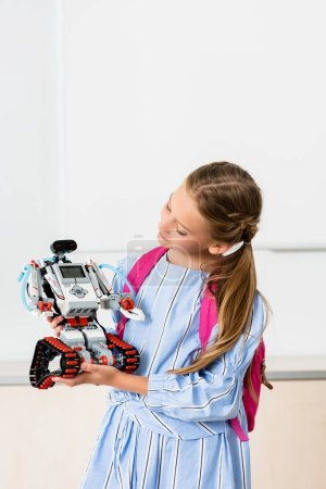 Photo for Schoolgirl with backpack holding robot in classroom of stem school - Royalty Free Image