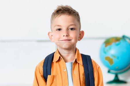 Photo pour Écolière avec sac à dos regardant la caméra en classe - image libre de droit