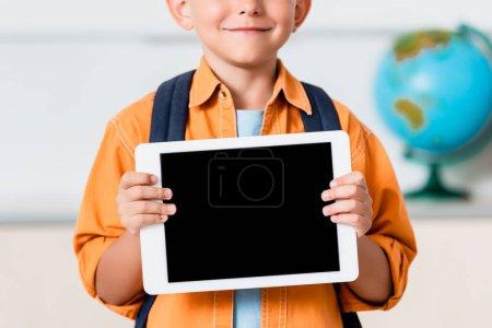 Photo pour Vue recadrée de l'écolier tenant tablette numérique avec écran blanc - image libre de droit