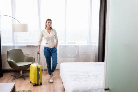 Photo pour Jeune femme debout avec la main dans la poche et bagages jaunes dans la chambre d'hôtel - image libre de droit