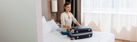 Photo for Horizontal image of young woman sitting on bed and looking at baggage in hotel room - Royalty Free Image