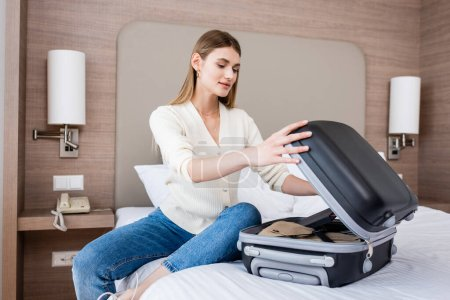 young woman sitting on bed and looking at luggage in hotel room