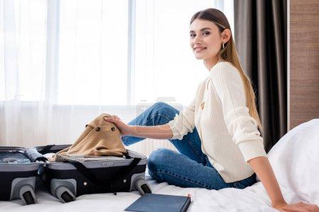 alegre joven sentada en la cama y sosteniendo la ropa cerca del equipaje en la habitación del hotel