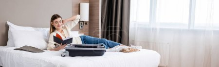 Photo for Panoramic concept of young woman looking at notebook near luggage on bed in hotel - Royalty Free Image