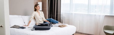 Photo for Panoramic concept of young woman looking away near notebook and luggage on bed in hotel - Royalty Free Image