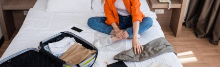 Photo for Panoramic crop of young woman touching clothing near baggage of bed in hotel - Royalty Free Image