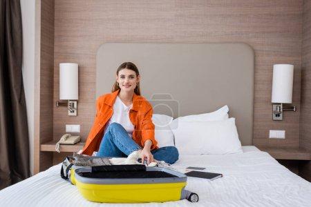 Photo pour Jeune femme assise sur le lit près des bagages jaunes et carnet à l'hôtel - image libre de droit