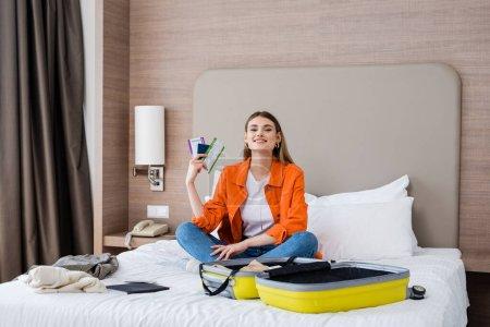 Photo pour Femme heureuse tenant passeport, carte d'embarquement et billet d'avion près des bagages et bloc-notes sur le lit dans l'hôtel - image libre de droit