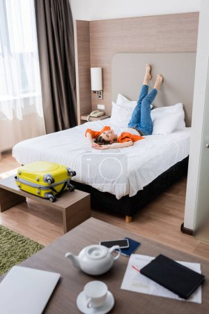 Photo for Selective focus of barefoot young woman resting on bed in modern hotel room - Royalty Free Image
