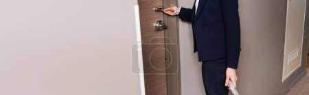 Photo for Panoramic crop of businesswoman in suit holding room card while unlocking door in hotel - Royalty Free Image