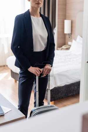 Photo for Cropped view of businesswoman in suit standing with luggage in hotel room - Royalty Free Image
