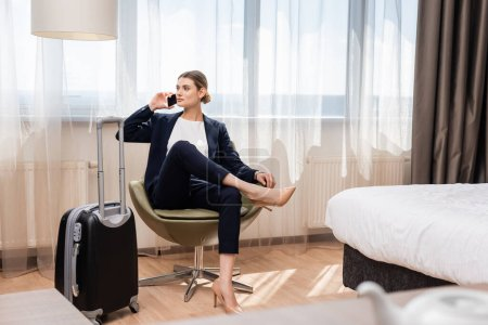 selective focus of businesswoman in suit talking on smartphone and sitting in armchair near baggage in hotel