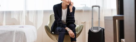 Photo for Horizontal crop of businesswoman in suit talking on smartphone and sitting in armchair near baggage in hotel - Royalty Free Image