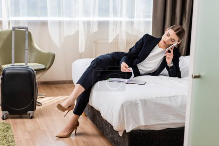 businesswoman in suit talking on smartphone and looking at notebook in hotel room