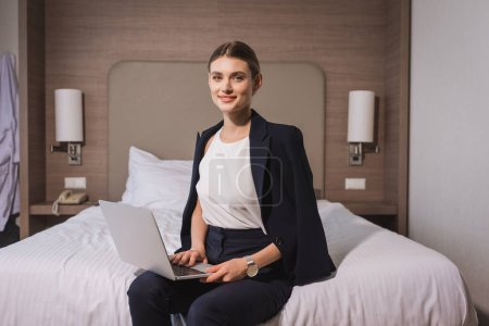 Photo for Joyful woman in suit sitting on bed with laptop in hotel room - Royalty Free Image
