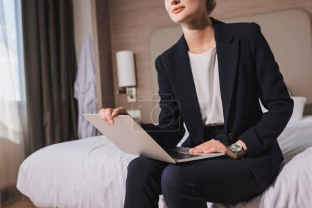 Photo for Cropped view of woman in suit sitting on bed with laptop in hotel room - Royalty Free Image