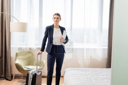 young businesswoman in suit standing with laptop and suitcase in hotel room
