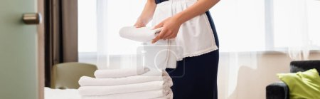 Photo for Cropped view of maid in apron holding clean towel in hotel room, panoramic shot - Royalty Free Image