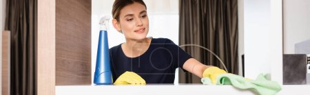 Photo for Panoramic crop of maid in rubber gloves holding rag while cleaning shelf in hotel room - Royalty Free Image