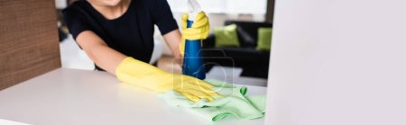 horizontal crop of maid in rubber gloves holding spray bottle and rag while cleaning shelf in hotel room
