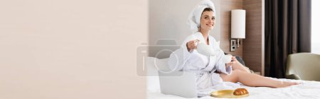 Photo for Panoramic crop of young woman in bathrobe holding cup and teapot near laptop and tray with breakfast - Royalty Free Image