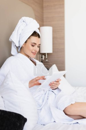 young woman in towel and white bathrobe looking at digital tablet in hotel room