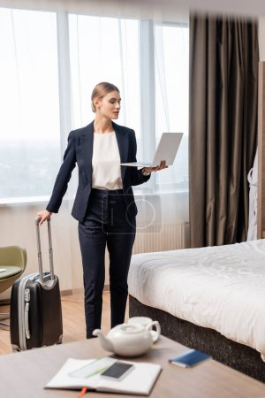 Photo pour Foyer sélectif de femme d'affaires en costume debout avec ordinateur portable et valise près du lit dans la chambre d'hôtel - image libre de droit