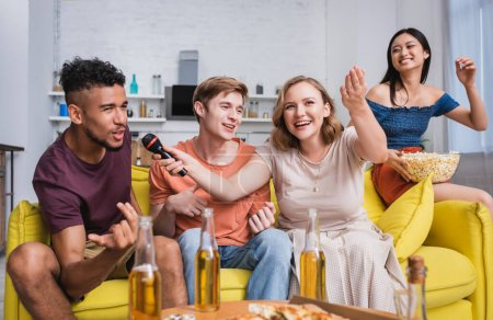 Photo for Excited multiethnic friends singing karaoke during party in kitchen - Royalty Free Image