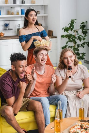 excited multiethnic friends applauding while singing karaoke during party
