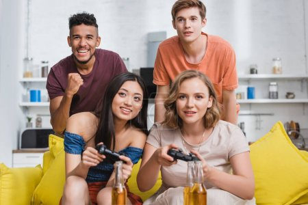 KYIV, UKRAINE - JULY 28, 2020: excited african american man showing winner gesture near multicultural friends playing video game