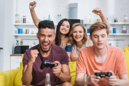 Photo for KYIV, UKRAINE - JULY 28, 2020: selective focus of excited women showing winner gesture near multicultural friends playing video game - Royalty Free Image