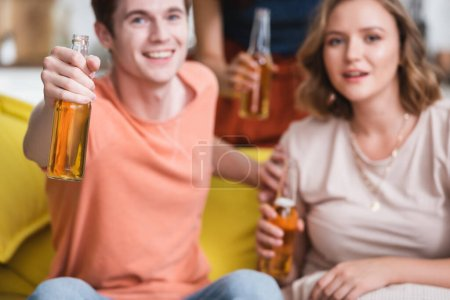 Photo for Selective focus of young man and woman holding bottles of beer and looking at camera during party - Royalty Free Image