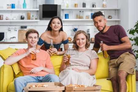 Photo for Joyful multiethnic friends with bottles of beer watching tv near pizza during party - Royalty Free Image