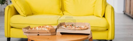 Photo for Panoramic crop of delicious pizza on table near yellow sofa - Royalty Free Image