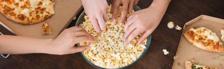 Photo pour Vue partielle d'amis multiculturels prenant du pop-corn dans un bol pendant la fête, concept horizontal - image libre de droit