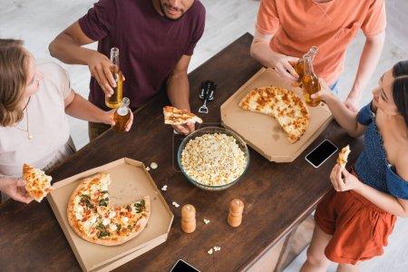 Photo pour Vue aérienne d'amis multiculturels claquant des bouteilles de bière près de la pizza pendant la fête - image libre de droit