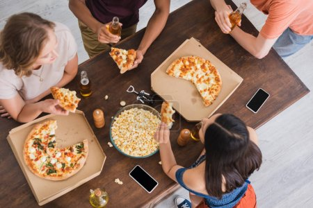 Photo for Top view of multiethnic friends drinking beer and eating pizza during party - Royalty Free Image