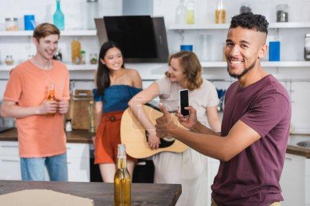 Photo pour Excité homme afro-américain montrant pouce levé tandis que la jeune femme jouer de la guitare pour des amis multiculturels - image libre de droit