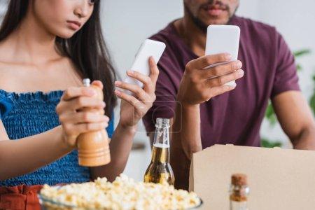 Photo pour Vue recadrée de interracial homme et femme bavarder sur smartphones pendant la fête - image libre de droit