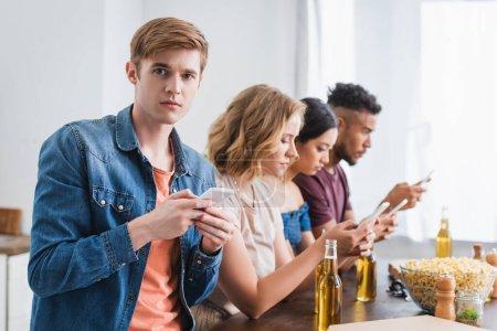 Photo pour Foyer sélectif d'amis multiculturels bavarder sur les téléphones mobiles près de la bière et du maïs soufflé pendant la fête - image libre de droit