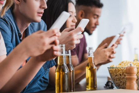 selective focus of multiethnic friends chatting on smartphones near beer during party