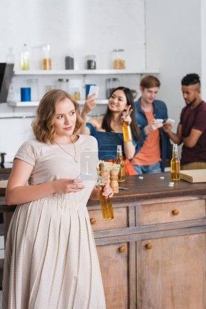 Photo pour Foyer sélectif de la jeune femme tenant de la bière et smartphone proches amis multiethniques sur fond - image libre de droit