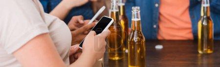 Photo pour Vue partielle d'amis multiethniques bavardant sur des smartphones près de la bière pendant la fête, culture horizontale - image libre de droit