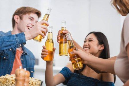 Photo pour Foyer sélectif d'amis multiethniques clinquant des bouteilles de bière pendant la fête - image libre de droit