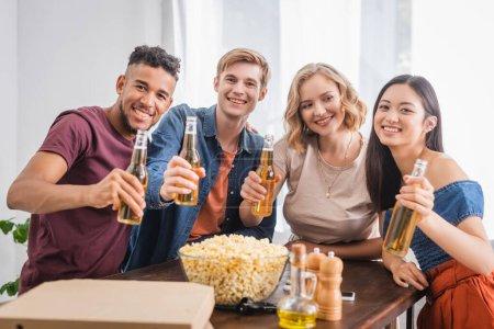 Photo pour Foyer sélectif de joyeux amis multiethniques regardant la caméra tout en tenant des bouteilles de bière - image libre de droit