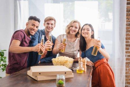 Photo pour Joyeux amis multiethniques regardant la caméra tout en tenant des bouteilles de bière - image libre de droit