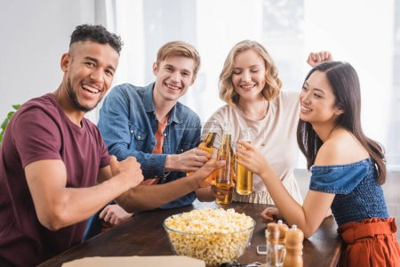 Photo for Joyful multicultural friends looking at camera while clinking bottles of beer - Royalty Free Image